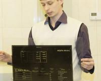 Иван Прокудин с фотоплёнкой-негативом, с которого изображение переносится на пластину. Фото Екатерины Антуфьевой