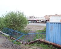 Место, где до 2010 года была лесенка с пандусом. Вот же  он, автовокзал, рядом! Но путь перегородили забором. А на днях  забор удлинили влево. Теперь и через трубу не перебраться. Фото Андрея Мирошникова