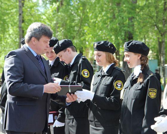 Заместитель председателя Совета депутатов Северодвинска Владимир Рудь вручает нагрудные знаки выпускникам. Фото автора