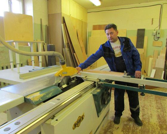 Столяр А. Середюк на распиловке ДСП. Рядом со станком (слева) натурный стул для школы искусств в Мирном.  Фото автора