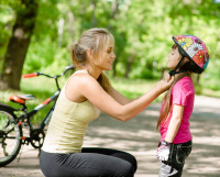 young mother dresses her daughter's bicycle helmet
