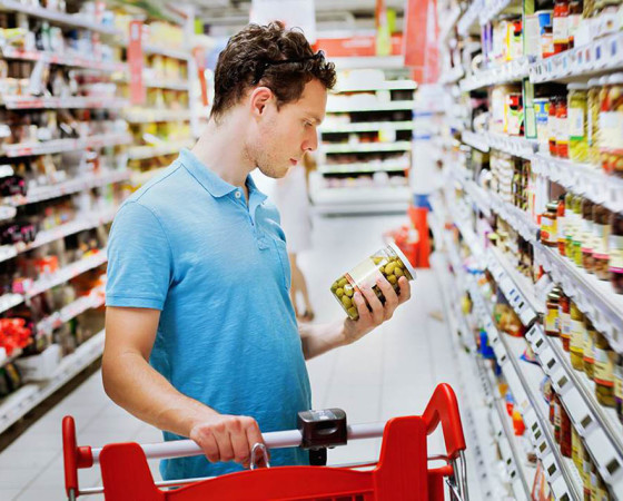 shopping concept, man reading label on the jar
